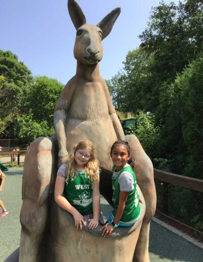 Two girl friends in a kangaroo statue pouch