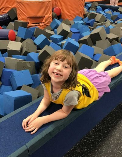 Girl posing in front of the foam play pit at Sky Zone