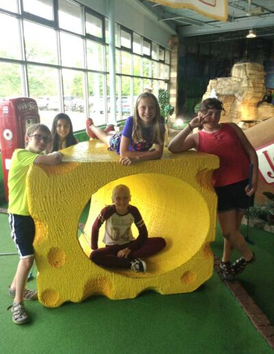 Friends posing around a cheese at an indoor golf course