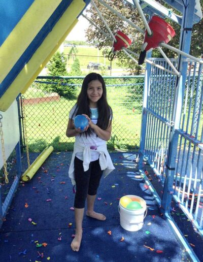 Girl getting ready to sling shot a water balloon