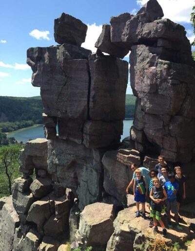 Kids posing by a rock formation while hiking
