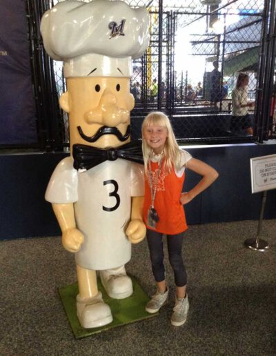 Girl posing with a Milwaukee Brewer Sausage Statue