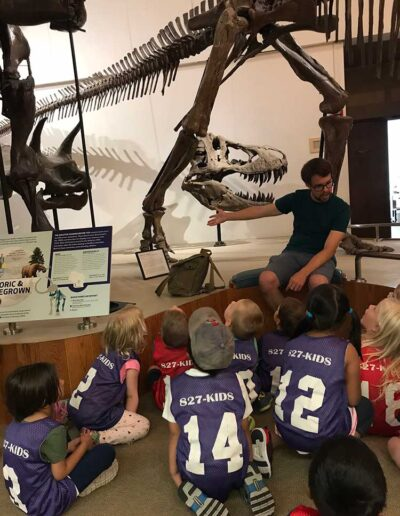 Children on a field trip learning about dinosaurs