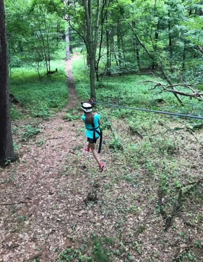 Girl zip-lining through a forest